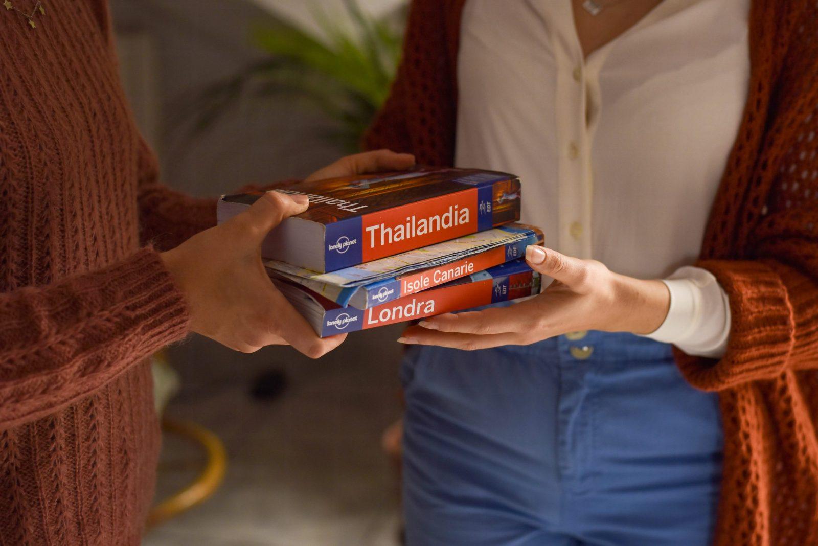 due mani che si scambiano libri di viaggio